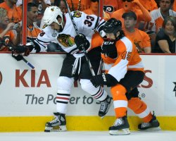 Flyers Arron Asham and Blackhawks Dustin Byfuglien flight for the puck during the 2010 Stanley Cup Final