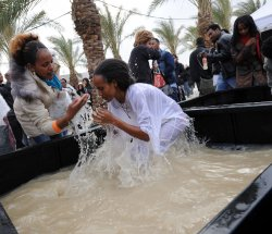 An Ethiopian Orthodox Christian prays in a tub filled with water from the Jordan River at Qasr el Yahud, Israel, on the feast of Epiphany