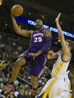 Phoenix Suns Vince Carter lays up the ball past Golden State Warriors David Lee in Oakland, California