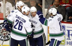Canucks celebrate goal against Blackhawks in Chicago
