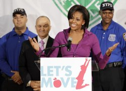 New York City Police Commissioner Ray Kelly watches First Lady Michelle Obama speak to Harlem children in New York
