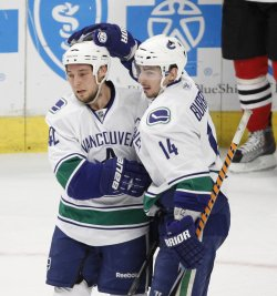 Canucks Wellwood and Burrows celebrate goal in Chicago
