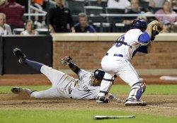 New York Yankees Curtis Granderson slides past New York Mets Josh Thole at Citi Field in New York