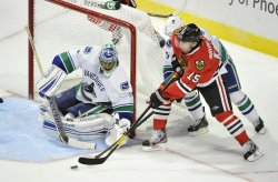 Canucks Luongo defends goal against Blackhawks Brunette in Chicago