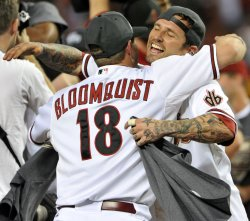 Diamondbacks Roberts and Bloomquist celebrate after winning the Western Division of the National League in Arizona