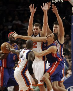 New York Knicks Nate Robinson, David Lee and Danilo Gallinari try to defend a pass by Detroit Pistons Austin Daye at Madison Square Garden in New York