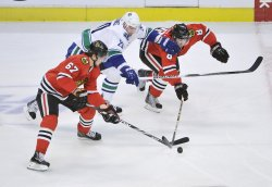 Blackhawks Frolik, Leddy and Canucks Higgins go for puck in Chicago