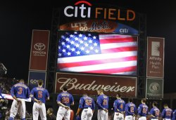 New York Mets stand on the first base line for the National Anthem