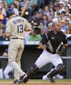 Rockies Catcher Olivo Looks for Loose Ball Against the Padres Denorfia in Denver