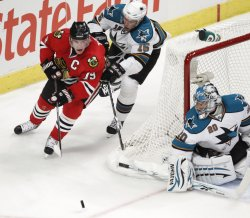 Blackhawks Toes moves the puck as Sharks Heatley and Nabokov defend in Chicago