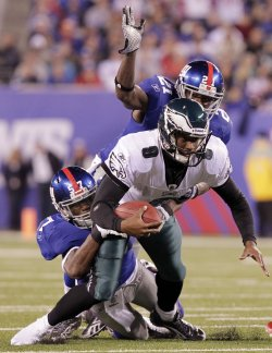 Philadelphia Eagles Vince Young scrambles for a 3 yard gain and is tackled by New York Giants Jacquian Williams at MetLife Stadium in New Jersey