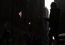 Pedestrians walk by a U.S Flag and the NYSE