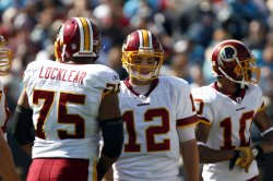 Washington Redskins quarterback John Beck (12) stands on the field with teammates Sean Locklear (75) and Jabar Gaffney (10)