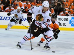 Blackhawks Ben Eager and Flyers Ville Leino fight for the puck during the 2010 Stanley Cup Final