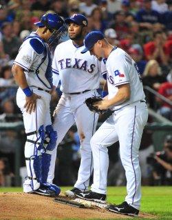 Rangers pitcher Matt Harrison catcher Yorvit Torrealba and shortstop Elvis Andrus meet on the mound during game 3 of the World Series in Texas