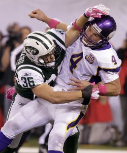 Minnesota Vikings quarterback Brett Favre gets hit after releasing a pass by New York Jets Jim Leonhard at New Meadowlands Stadium in New Jersey