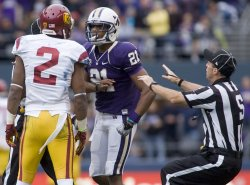 Washington Huskies' defensive back MArcus Peters (21) is separated from USC Trojans wide receiver Robert Woods by Side Judge Aaron Santi at CenturyLink Field in Seattle