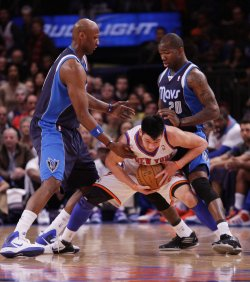 New York Knicks Jeremy Lin tries to break free from Dallas Mavericks Dominique Jones and Lamar Odom at Madison Square Garden in New York