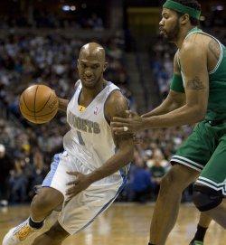 Nuggets Billups Drives Against Celtics Wallace in Denver