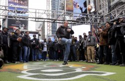 "Former Buffalo Bills quarterback Jim Kelly kicks a field goal at the ""Tostitos Fiesta in the Square"" in New York"