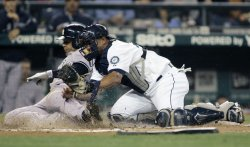Mariners' Miguel Olivo tags out Yankees' Andruw Jones in third inning in Seattle.