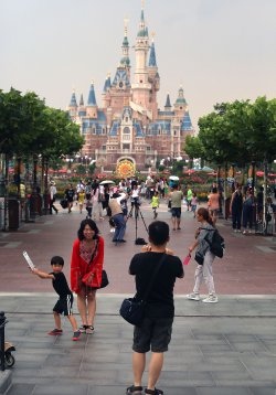 Chinese tourists pose for photos in front of Shanghai Disneyland Resort's castle, China