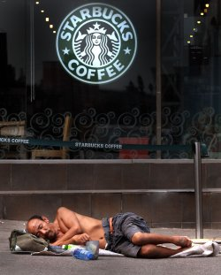 An elderly Chinese man sleeps in front of a Starbucks in Beijing