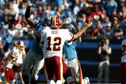 Washington Redskins quarterback John Beck (12) looks to pass around the Carolina Panthers defenders