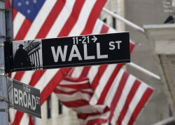 An American Flag is behind the street sign for Wall Street