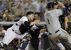 Milwaukee Brewers Corey Hart is tagged out at home plate by New York Yankees Russell Martin at Yankee Stadium in New York