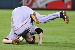 Giants' Freddy Sanchez rolls onto his head in game 4 of the World Series in Texas