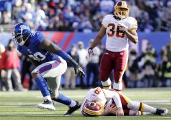 Washington Redskins Rex Grossman is sacked for a an 8 yard loss by New York Giants Jason Pierre-Paul at MetLife Stadium in New Jersey