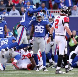 Atlanta Falcons Matt Ryan walks to the sidelines while New York Giants Aaron Ross and Michael Johnson react after a defensive stand on third down in the second quarter of week 11 of the NFL season at Giants Stadium in East Rutherford, New Jersey