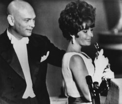 Actress Elizabeth Taylor holds her first Oscar, next to presenter Yul Brynner