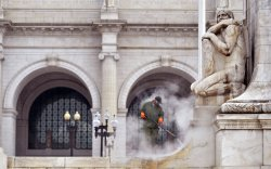 A worker cleans the Christopher Columbus Fountain in Washington