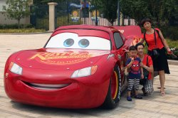 """Chinese pose for a photo next to a model from the movie """"Cars"""" in Shanghai, China"""