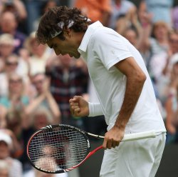 Roger Federer celebrates winning a point on the first day of Wimbledon.
