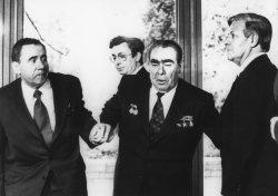 Andrei Gromyko and Helmut Schmidt help Soviet President Leonid Brezhnev to his feet