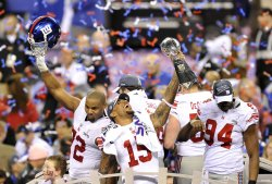 Thomas holds the Lombardi trophy while teammates celebrate
