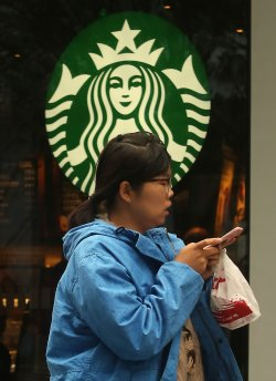 A Chinese woman walks past a Starbucks in central Beijing