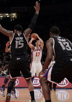 New York Knicks Jeremy Lin shoots between Sacramento Kings Demarcus Cousins and Tyreke Evans at Madison Square Garden in New York