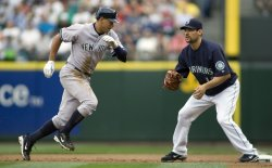 Seattle Mariners' first baseman Casey Kotchman (R) waits for the throw as New York Yankees' Alex Rodriques makes it back to the bag in Seattle.