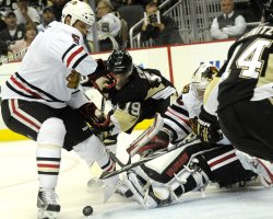 Blackhawks Alec Richards Clears Puck Away From Pens Mike Comrie in Pittsburgh
