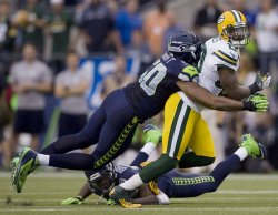 Green Bay Packer wide receiver James Jones is tackled by Seattle Seahawks' linebacker K.J. Wright and cornerback Brandon Browner at CenturyLink Field in Seattle.