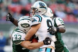 Carolina Panthers Gary Barnidge reacts while being tackled by New York Jets Eric Smith and David Harris in week 12 of the NFL season at Giants Stadium