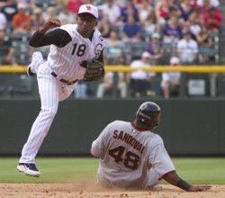 Rockies Herrera Completes Double Play Over Giants Sandoval in Denver