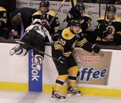 Penguins Asham checked by Bruins Paille at TD Garden in Boston, MA.
