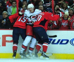 Washington Capitals' Matt Bradley and Boyd Gordon sandwich Carolina Hurricanes' Jussi Jokinen in Washington