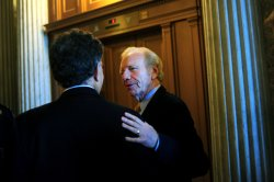 Sen. Joe Lieberman greets Sen. Al Franken prior to voting on the debt limit and reduction bill in Washington