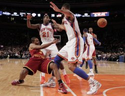 Cleveland Cavaliers Ramon Sessions passes the ball between New York Knicks Iman Shumpert and Jared Jeffries at Madison Square Garden in New York